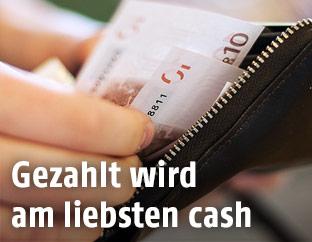 frau nimmt Geldscheine aus einem Geldbörsel
