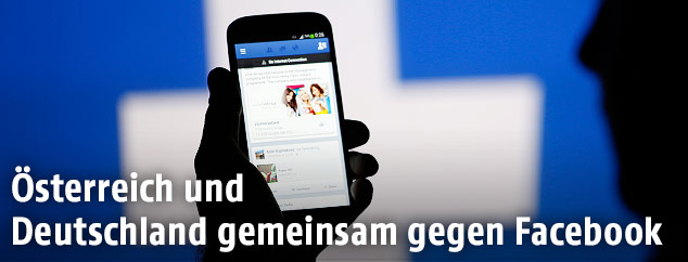Hand hält Smartphone vor Facebook-Logo