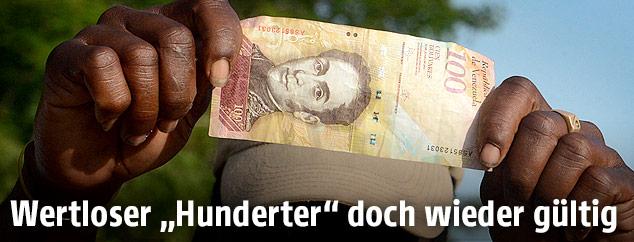 Mann zeigt eine 100-Bolivar Banknote