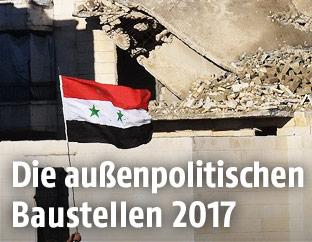 Sysrische Fahne vor einer Häuserruine in Aleppo