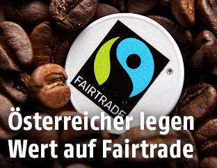 Fairtrade-Logo zwischen Kaffeebohnen