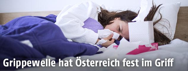 Frau liegt krank im Bett