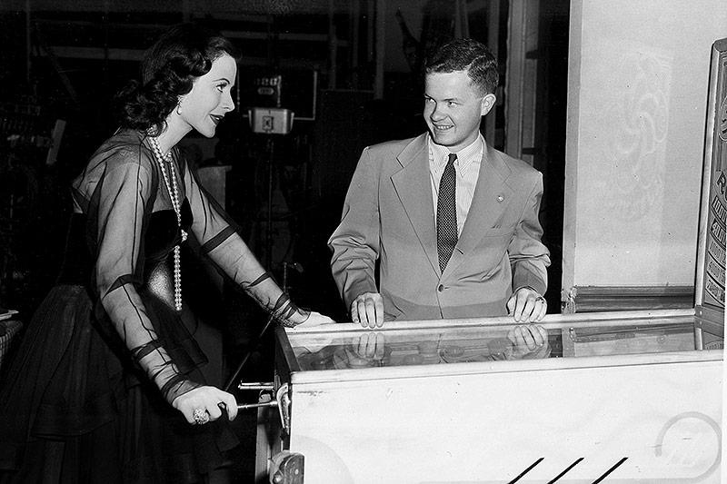 Schauspielerin Hedy Lamarr spielt mit einem Flipperautomat