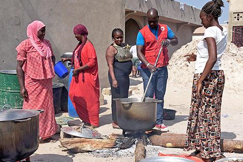 Rot-Kreuz-Mitarbeiter mit gambischen Flüchtlingen