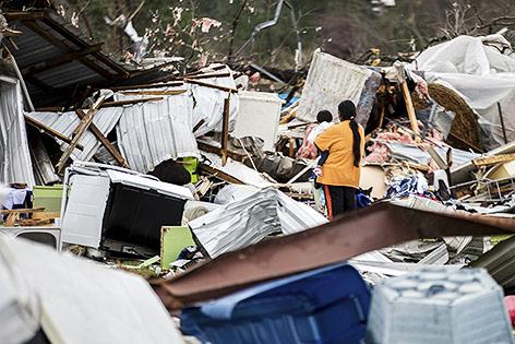 Frau mit Kind im Arm steht vor den Trümmern eines Hauses
