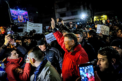 Demonstranten grüßen Staatspräsident Klaus Iohannis in ihrer Mitte in Bukarest