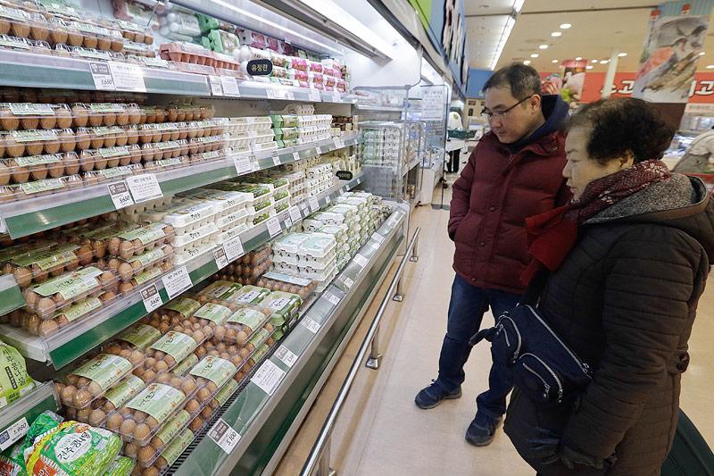 Kunden vor dem Eierregal im Supermarkt