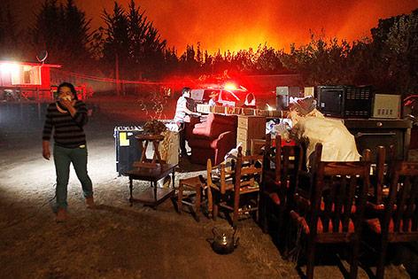 Eine Frau bringt Einrichtungsgegenstände vor dem Waldbrand in Sicherheit