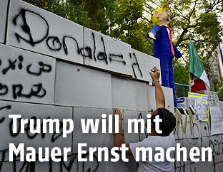 Demonstrant vor einer Mauer aus Karton