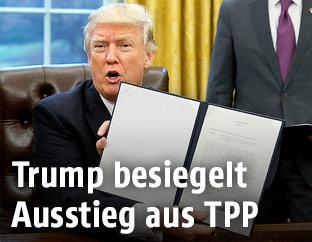 US-Präsident Trump hält das Abkommen in die Kamera