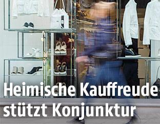 Zwei Frauen gehen vor einem Geschäft in einer Einkaufsstraße