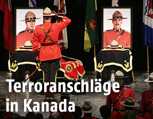 Ein kanadischer Polizist salutiert vor den Bildern ermordeter Kollegen
