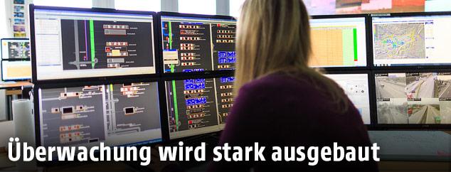 Frau blickt auf mehrere Überwachungsbildschirme