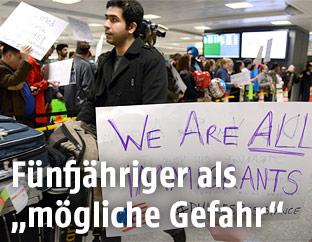 Passagiere mit Protestschildern auf dem Flughafen Dulles