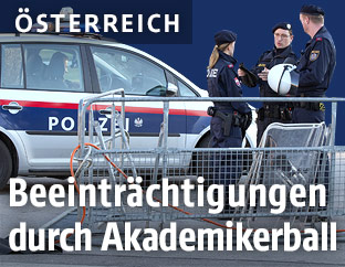 Polizisten und Polizeiwagen hinter einer Absperrung am Ring in Wien