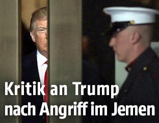 US-Präsident Donald Trump hinter einer Tür, davor stehen Soldaten