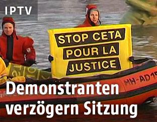 Demonstranten halten ein Schild gegen CETA in die Höhe