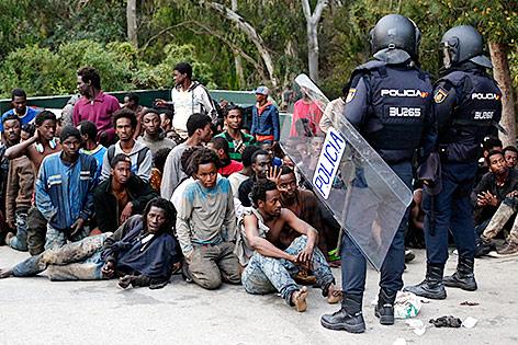 Migranten und spanische Polizisten in Ceuta