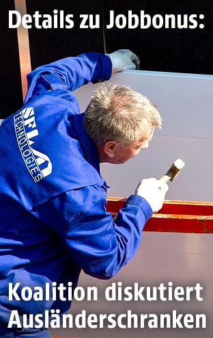 Mann arbeitet an einer Fassade