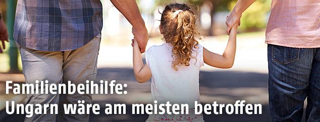 Ein Kind geht Hand in Hand mit Vater und Mutter auf einem Weg spazieren