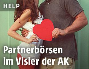 Ein Mann und eine Frau halten ein rotes Herz