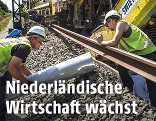 Zwei Arbeiter verlegen Schienen