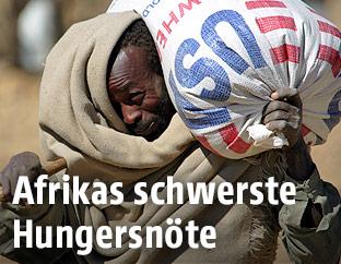 Ein Mann trägt einen Sack mit Weizenmehl auf dem Rücken