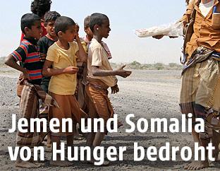 Ein Mann gibt jemenitischen Kindern zu essen