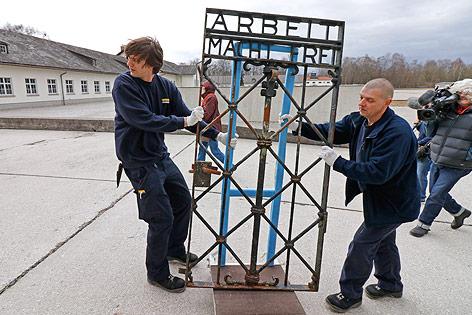 """Arbeiter transportieren ein Tor mit der Aufschrift """"Arbeit macht frei"""""""