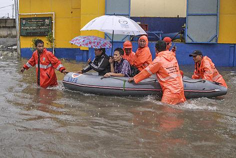 Rettungskräfte mit Rettungsboot im überschwemmten Jakarta