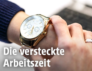 Frau sieht im Büro auf ihre Uhr