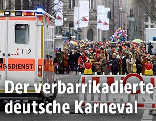 Rettungswagen neben einer Straßensperre während des Karneval