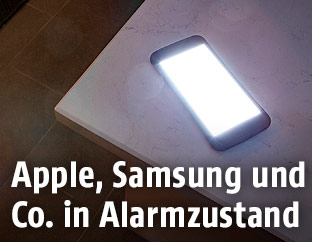 Leuchtendes Handy am Tisch