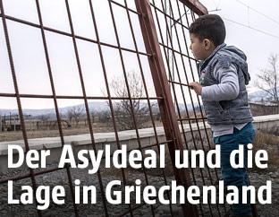 Kleines Kind blickt durch einen Zaun