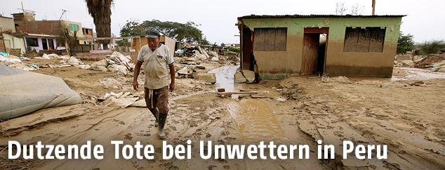 Ein Mann vor einem zerstörten Haus
