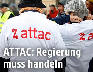 Personen tragen T-Shirts mit Attac-Logo