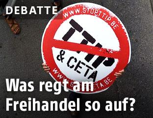 Demonstrant hält ein Schild mit durchgestrichenem Schriftzug TTIP & CETA in die Höhe