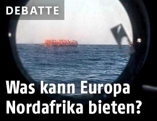 Flüchtlinge auf einem Schlauchboot durch eine Schiffsluke gesehen