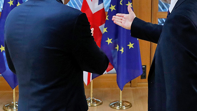 Zwei Männer im Gespräch vor einer EU-Flagge und einer Union-Jack-Flagge