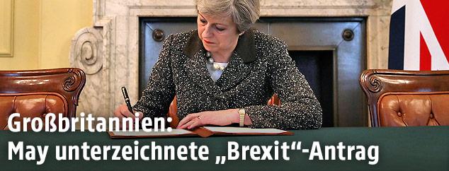 Die britische Premierministerin Theresa May unterschreibt