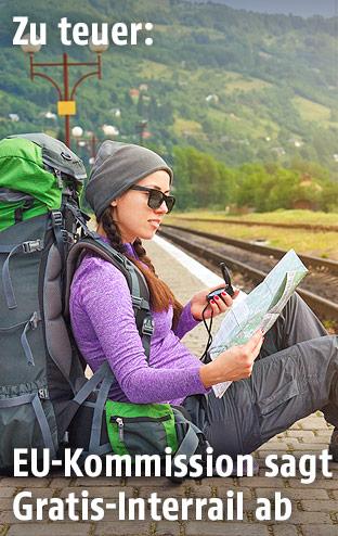 Eine Rucksacktouristin sitzt am Bahnsteig
