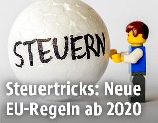 """Legomännchen mit einer Styroporkugel auf der """"Steuern"""" draufsteht"""