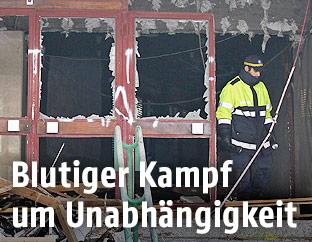 Ein Polizist neben einer von einer Bombenexplosion zerstörten Tür