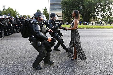 Archivbild zeigt eine junge Frau im Sommerkleid vor zwei Polizisten