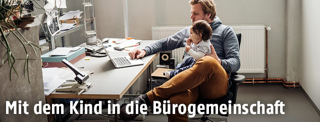 Mann mit Kind arbeitet am Laptop