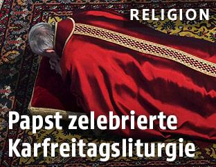 Papst Franziskus liegt mit dem Bauch auf dem Boden und betet