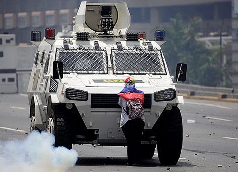 Frau steht vor Panzerfahrzeug in Caracas