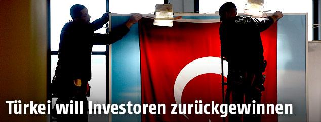 Arbeiter beim Aufhängene einer türkischen Fahne