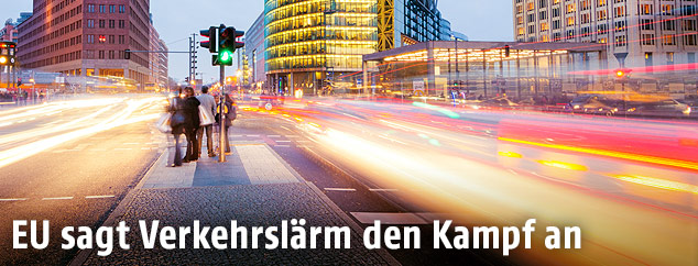 Autolichter auf einer stark frequentierten Straße und Fußgänger auf einer Verkehrsinsel