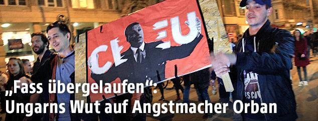 """Demonstranten mit einem Plakat, auf dem Staatschef Viktor Orban den Schriftzug """"CEU"""" zerreißt"""